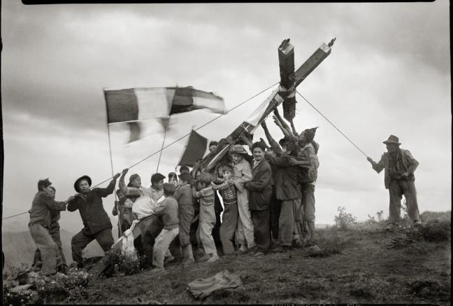 "Quechuan men are erecting a large cross for teh ""Fiesta de la cruz"" (Festival of the cross)"
