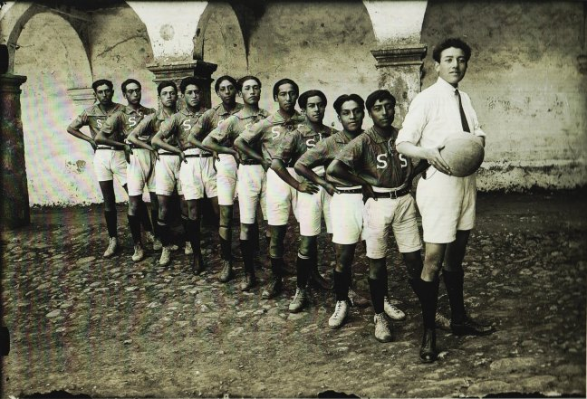 Quechuan male sports team. One of them holds a futbal