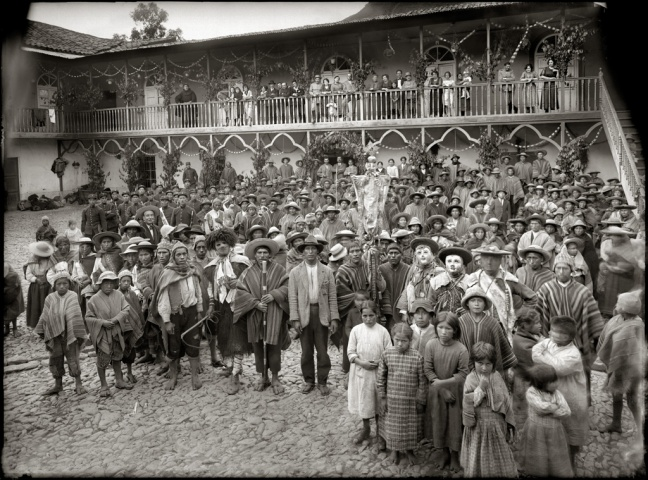 Dozens of Quechuan villagers stand in front of a colonial building