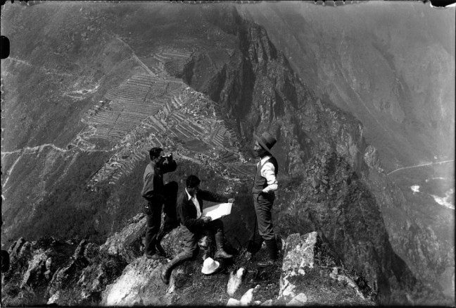 Quechuan men stand on top of a cliff, with huge mountains in the back