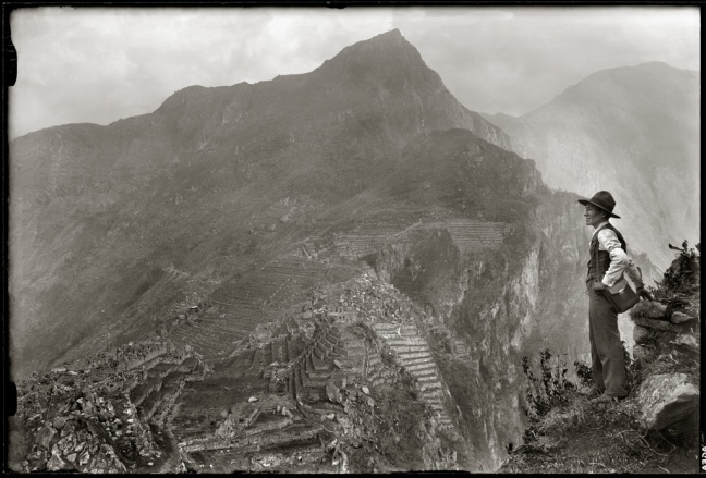 A Quechuan man stands to the side of the Hyana Picchu mountains