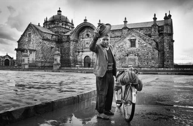 Quechuan man next to his bike. A Christian building in the background