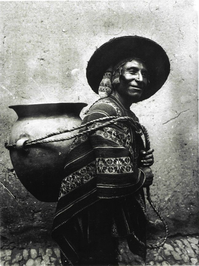 Quechuan man has a large jar strapped to his back. He is smiling