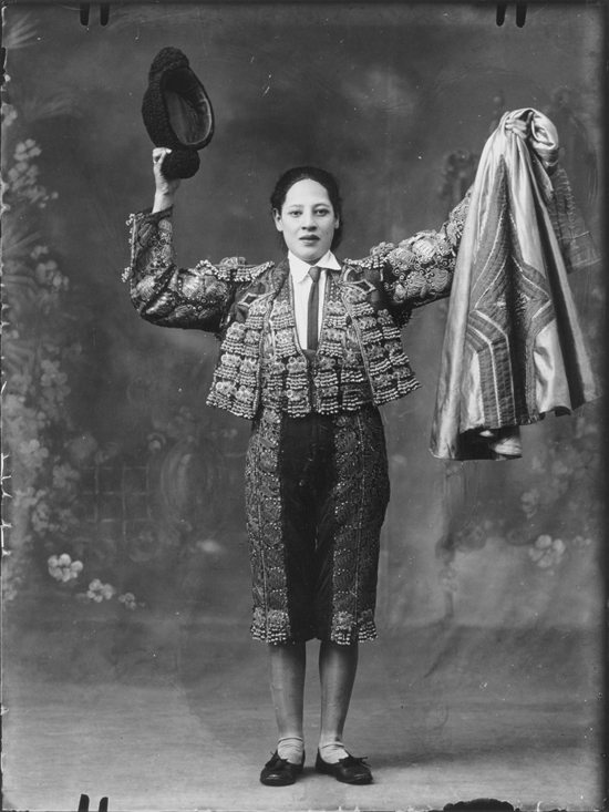 Matadora - a Spanish woman is dressed as a matador. She holds her cloak in the air