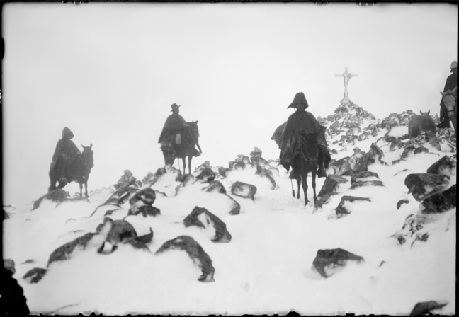 A blurry photo of three Quechuan people in a snowy mountain. A large cross is in the far background