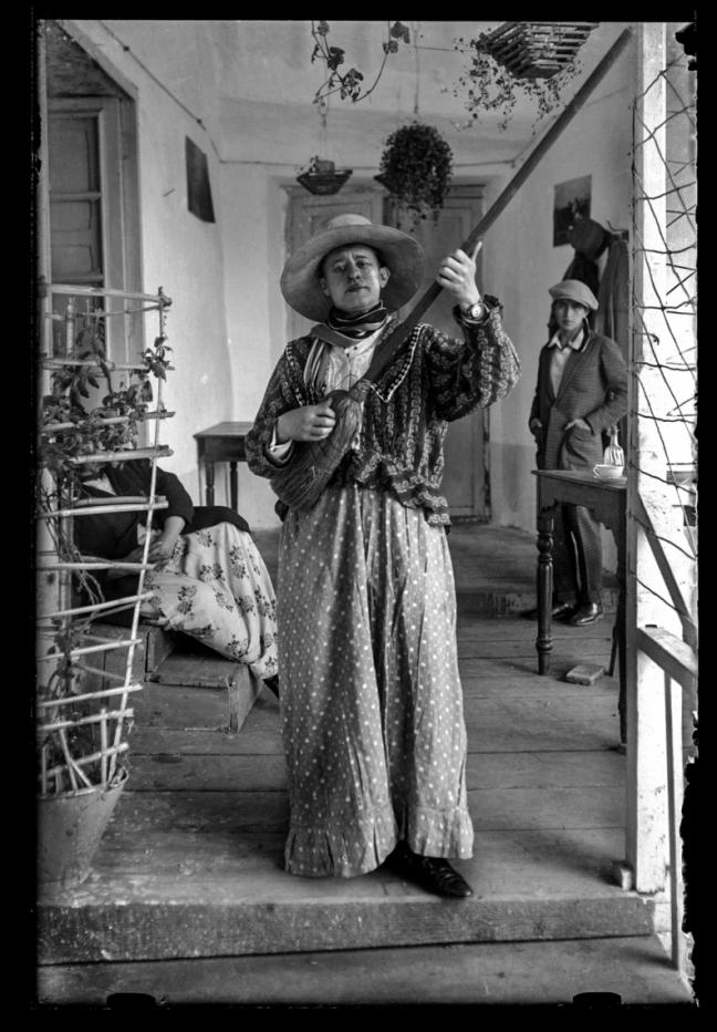 Quechuan woman pretends to play a broom like a guitar