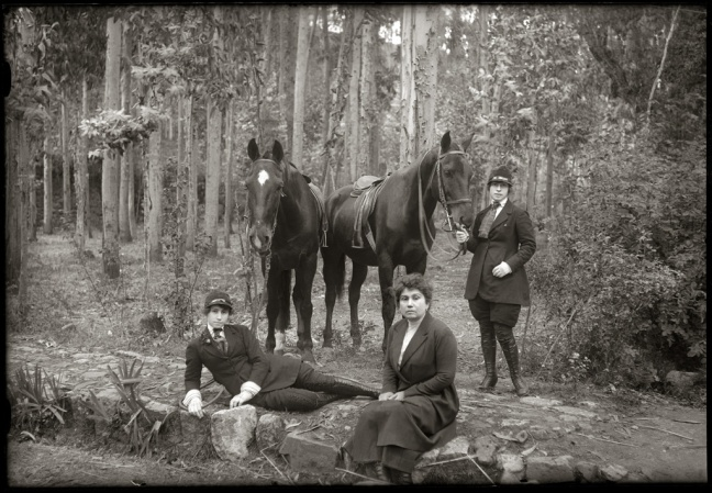 Mestiza women are dressed in modern 1920s riding gear. Two are sitting and laying on the ground. Another woman stands next to two horses