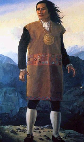 Painting of Tupac Amaru. He is a Quechuan man with Brown skin. He wears a large gold medallion of the sun god Inti, and a traditional dress with modern shoes